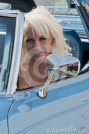 Blond smiling woman in a car