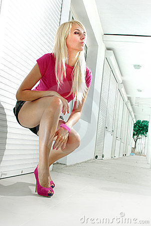 Blond squatting on white