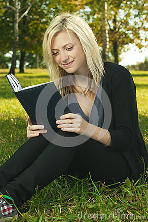 Blond student girl reading book