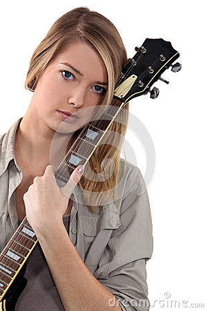 Blond teenage girl posing with guitar