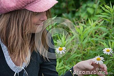 Blond Woman Admiring Springtime Daisy