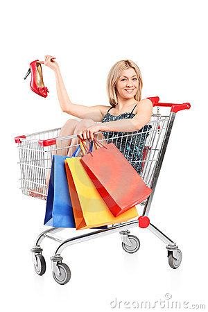 Blond woman with bags posing into a shopping cart
