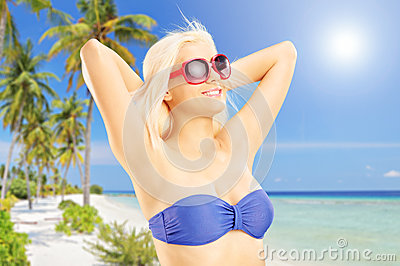 Blond woman in bikini relaxing on a tropical beach