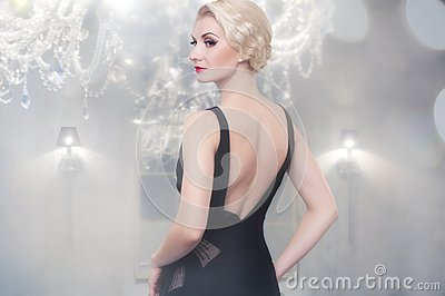 Blond woman in black dress indoors