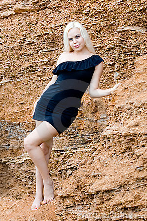 Blond woman in black dress among rocks