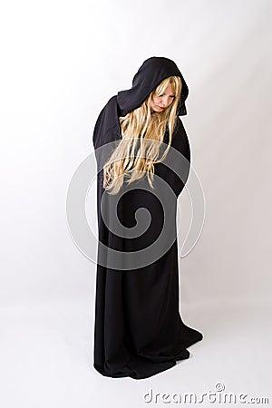 Blond woman in black hooded cloak looking down