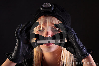Blond woman cat burglar using a spy camera