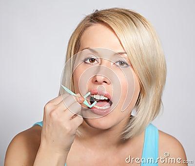 blond woman  checks her teeth