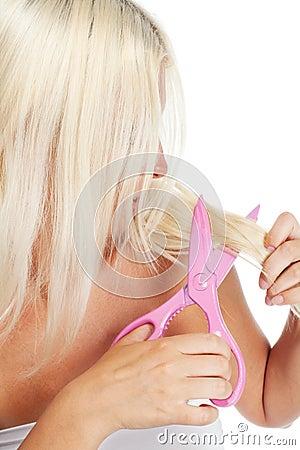 Blond woman cutting her hair