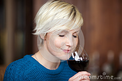 Blond Woman Drinking Red Wine In Restaurant