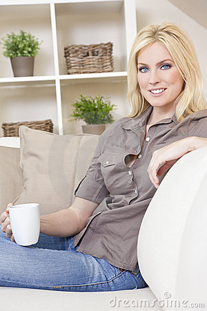 Blond Woman Drinking Tea or Coffee At Home