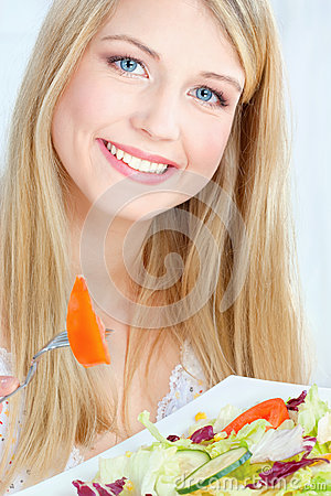 Blond woman eating salad
