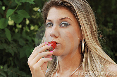 Blond woman eating strawberry