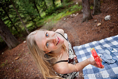 Blond woman eating watermelon while picnic