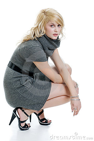Blond woman with grey dress squatting