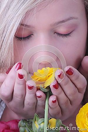 Blond woman hiding behind colorfoul flowers