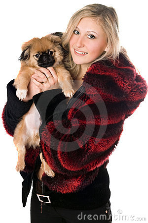 Blond woman holding a pekinese puppy