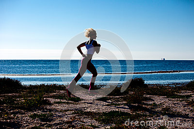 Blond Woman Jogging On The Beach