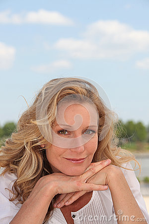 Blond woman by a lake