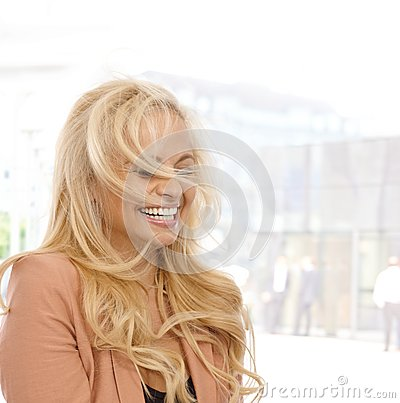 Blond woman laughing outdoors