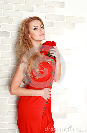 Blond woman with red rose in studio, girl and flower