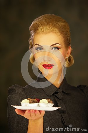 Blond woman in retro dress with plate of sweets