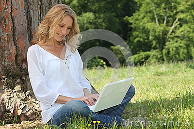 Blond woman sat by tree
