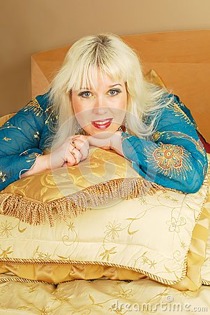 Blond woman sitting  with pillows on a bed