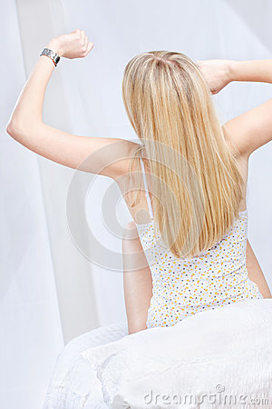 Blond woman stretching and looking at the clock