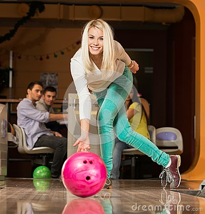 Blond woman throwing bowling ball