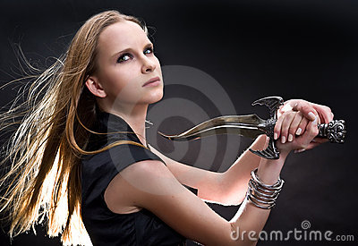 Blond young girl holding dagger