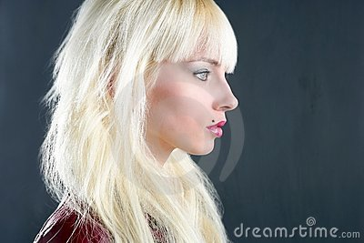 Blond young girl profile portrait over gray