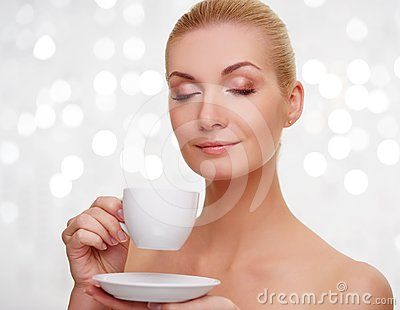Blond young woman holding cup of coffee