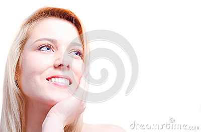 Beautiful Caucasian woman caressing her face and smiling towards a copy space