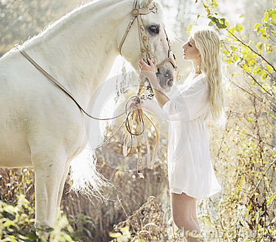 Blonde beautiful woman touching mejestic horse