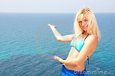 Blonde in bikini inviting to sea