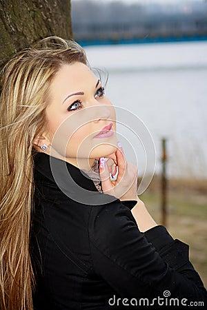 Blonde in black raincoat