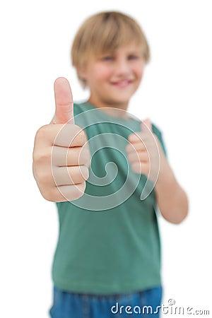Blonde boy giving thumbs up focus shot