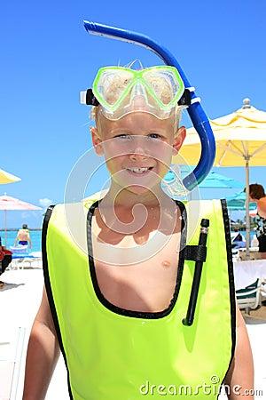 Blonde boy wearing snorkel gear at the beach