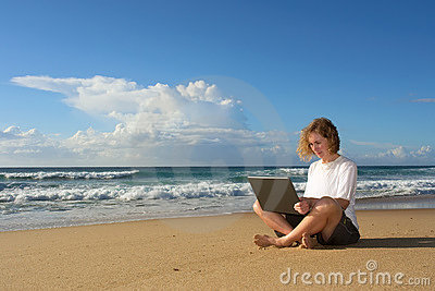 Blonde businesswoman sits with notebook on beach