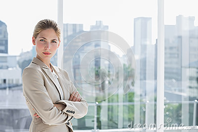 Blonde businesswoman standing with arms crossed