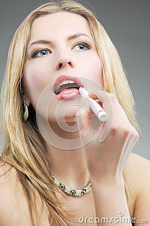 Blonde doing makeup with makeup stick