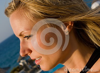 Blonde female looking into sun in resort