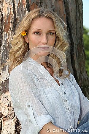 Blonde Frau durch einen Baum