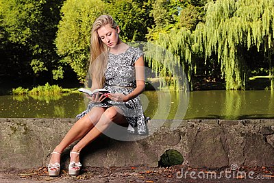 Blonde girl with book on green background of city park