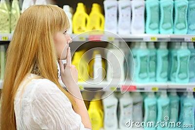 Blonde girl chooses abstergent in shop