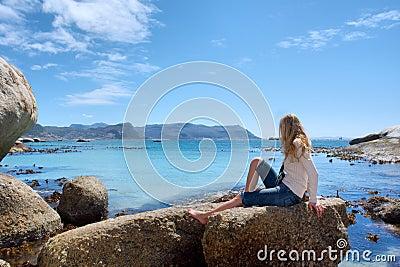 Blonde girl enjoys sun on rocky beach