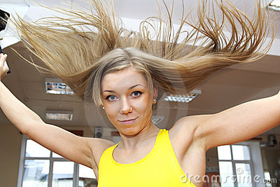 Blonde girl with flying hair jumping in gym