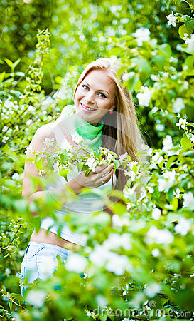 Blonde girl in the garden on a sunny day