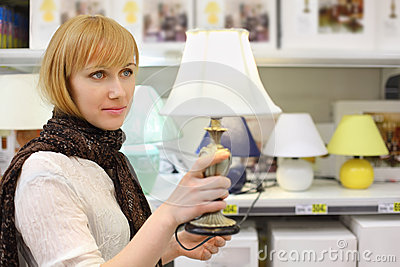 Blonde girl holds beautiful table lamp in shop
